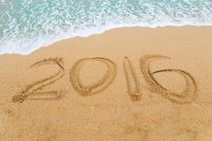 Aufschrift 2016 geschrieben auf sandigen Strand mit dem Wellennähern Stockbilder