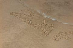 Aufschrift 2017 geschrieben auf sandigen Strand mit dem Wellennähern Lizenzfreie Stockbilder
