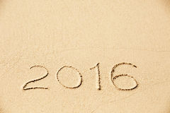 Aufschrift 2016 geschrieben in den nassen gelben Strandsand Lizenzfreie Stockbilder