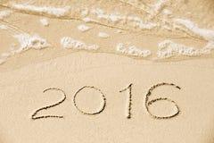Aufschrift 2016 geschrieben in den nassen gelben Strandsand, der Wäsche ist Stockbild