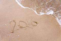 Aufschrift geschrieben in den nassen Strandsand, der mit Meerwasserwelle gewaschen wird Setzen Sie Konzept feiernd überschreiten  Lizenzfreie Stockfotos