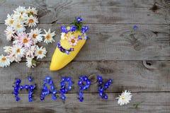 Aufschrift ` glückliches ` von den Blumen auf hölzernem Hintergrund mit Pfeffer in der Form von Emoticon, mit Kopienraum Lizenzfreie Stockfotos