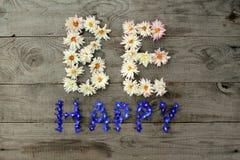 Aufschrift ` ist glückliches ` von den Blumen auf hölzernem Hintergrund Stockfotos
