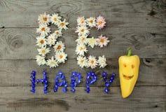 Aufschrift ` ist glückliches ` von den Blumen auf hölzernem Hintergrund mit Pfeffer in der Form von Emoticon Stockfotos
