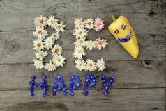 Aufschrift ` ist glückliches ` von den Blumen auf hölzernem Hintergrund mit Pfeffer in der Form von Emoticon Stockfotografie
