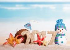 Aufschrift 2017, Kokosnuss, Starfish, Blume, Schneemann im Sand gegen Meer Lizenzfreies Stockfoto