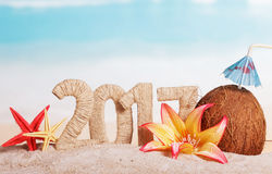 Aufschrift 2017, Kokosnuss, Starfish und Blumen des neuen Jahres auf Meer Lizenzfreies Stockfoto