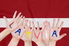 Aufschrift Lettland auf den Händen der Kinder vor dem hintergrund einer wellenartig bewegenden Flagge des Lettlands stockfoto