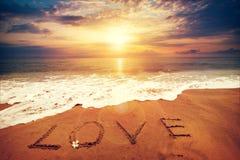 Aufschrift LIEBE geschrieben auf den sandigen Strand mit Meereswogen - Sonnenuntergangzeit Stockfotografie
