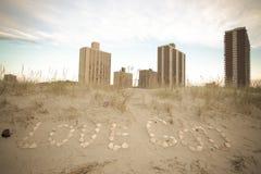 Aufschrift-Liebes-Gott von Muscheln im Sand auf der Küste Stockfotos