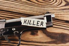 Aufschrift MÖRDER auf heftigem Papier und glatter Pistole stockfoto