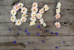 Aufschrift ` O.K.! ` von den Blumen auf hölzernem Hintergrund mit zerstreuten Blumen und Kopienraum Lizenzfreie Stockfotografie