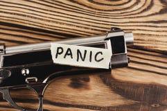 Aufschrift PANIK auf heftigem Papier und glatter Pistole stockfotografie
