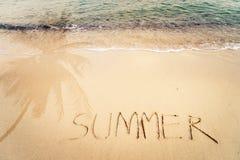 Aufschrift-Sommer geschrieben auf den sandigen Strand mit Meereswogen und Palmeschatten Stockbilder