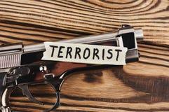 Aufschrift TERRORIST auf heftigem Papier und glatter Pistole stockbilder