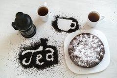 Aufschrift und Bild einer Schale des verschütteten Teeblatts, der Schalen und des Kuchens Lizenzfreie Stockbilder