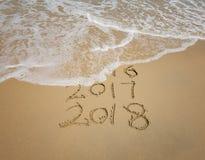 Aufschrift 2018 und 2017 geschrieben in den nassen Strandsand Stockfoto