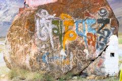 Aufschrift von den tibetanischen Symbolen auf einem Stein lizenzfreies stockfoto