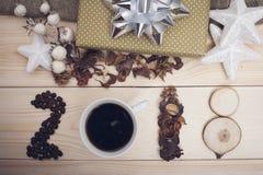 Aufschrift 2018 von Kaffeebohnen, von Kaffeetasse, von trockenen Blumen und von hölzernen Scheiben Stockbild