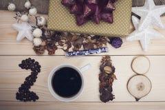 Aufschrift 2018 von Kaffeebohnen, von Kaffeetasse, von trockenen Blumen und von hölzernen Scheiben Lizenzfreies Stockfoto