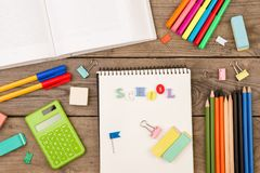 Aufschrift von u. x22; school& x22; , Buch, Taschenrechner, Notizblock und anderes Briefpapier auf braunem Holztisch Stockbild