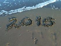 Aufschriftjahr 2015 im Sand des Meeres mit Wellen Stockfotografie