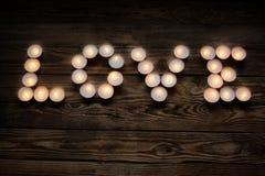 Aufschriftliebe von den Kerzen auf hölzernem Hintergrund Stockbilder