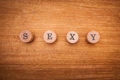 Aufschriftsexy bestanden aus hölzernen Buchstaben auf einem hölzernen Hintergrund Zeigt Mut, Schönheit, Geheimnis an stockfotografie