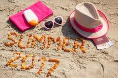 Aufschriftsommer 2017, Zubehör für das Ein Sonnenbad nehmen und Pass mit den Währungen Euro auf Sand am Strand, Sommerzeit Stockbilder