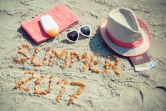 Aufschriftsommer 2017, Zubehör für das Ein Sonnenbad nehmen und Pass mit den Währungen Euro auf Sand am Strand, Sommerzeit Stockfotos