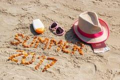 Aufschriftsommer 2017, Zubehör für das Ein Sonnenbad nehmen und Pass mit den Währungen Euro auf Sand am Strand, Sommerzeit Lizenzfreie Stockfotos