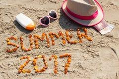 Aufschriftsommer 2017, Zubehör für das Ein Sonnenbad nehmen und Pass mit den Währungen Euro auf Sand am Strand, Sommerzeit Stockfotografie