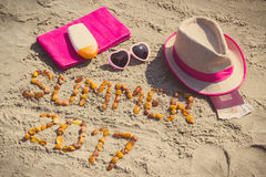 Aufschriftsommer 2017, Zubehör für das Ein Sonnenbad nehmen und Pass mit den Währungen Euro auf Sand am Strand, Sommerzeit Lizenzfreies Stockfoto