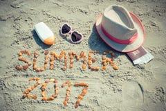 Aufschriftsommer 2017, Zubehör für das Ein Sonnenbad nehmen und Pass mit Währungsdollar auf Sand am Strand, Sommerzeit Lizenzfreie Stockfotos