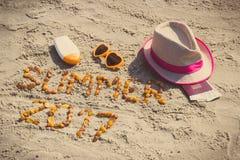 Aufschriftsommer 2017, Zubehör für das Ein Sonnenbad nehmen und Pass mit Währungsdollar auf Sand am Strand, Sommerzeit Lizenzfreies Stockbild