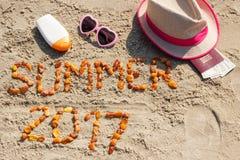 Aufschriftsommer 2017, Zubehör für das Ein Sonnenbad nehmen und Pass mit Währungsdollar auf Sand am Strand, Sommerzeit Lizenzfreie Stockfotografie