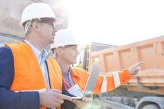 Aufsichtskraft, die dem Kollegen etwas hält Laptop an der Baustelle zeigt Lizenzfreies Stockfoto