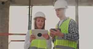 Aufsichtskraft eines errichtenden im Bau Mannes, der mit Ingenieurdesignerfrau den Fortschritt des Baus bespricht und stock video footage