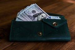 aufspeicherung Viele Dollar im grünen Geldbeutel Lizenzfreie Stockfotos