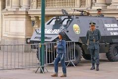 Aufstandpolizei steht betriebsbereiten nahen Panzerkampfwagen Lizenzfreie Stockbilder