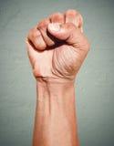 Aufstandprotestfaust angehoben in die Luft Männliche geballte Faust auf dunklem Schmutzhintergrund Lizenzfreies Stockbild