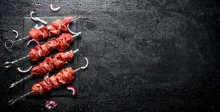 Aufsteckspindel mit rohem Kebab und Zwiebel lizenzfreies stockfoto