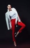 Aufstellung der eleganten Frau in den roten Hosen und im weißen Mantel stockbilder