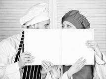 Aufstellung der Handelsbilanz im Restaurant Chef und Vorbereitungskoch, der leeres Kontoblatt h?lt Vorlagenausf?hrungsbuch des ko lizenzfreie stockfotos