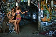 Aufstellung mit zwei Badeanzugmodellen sexy vor Graffitihintergrund mit Marineartzusätzen Stockfoto