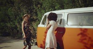 Aufstellung schöne junge Frau vor ihrer afrikanischen Freundfrau, hinter dem Retro- Bus-, Lächeln und Tanzennehmen stock video footage