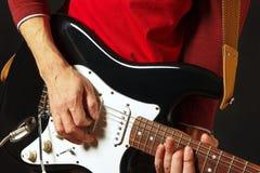 Aufstellung von den Händen des Gitarristen die E-Gitarre auf schwarzem Hintergrund spielend Lizenzfreie Stockfotos