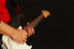 Aufstellung von den Händen des Gitarristen die Gitarre auf schwarzem Hintergrund spielend Stockbilder