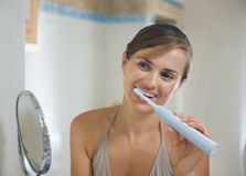 Auftragende Zähne der Frau mit elektrischer Zahnbürste Stockfoto