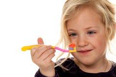 Auftragende Zähne des Kindes. Zahnbürste und Zahnpasta Stockbild